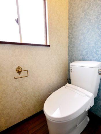 長岡京市の中古住宅丸ごとリフォーム。リフォーム後のトイレです。奥様のお気に入りのヴィクトリア調のクロスをベージュとブルーの色違いで使われています。洗面室の背面には、淡いシルバーの色違いが貼られています。
