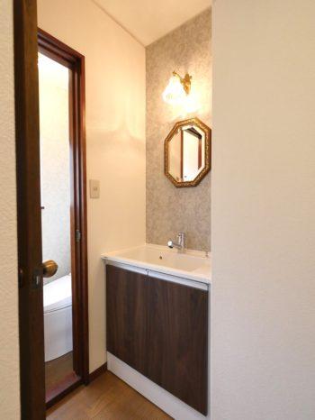 長岡京市の中古住宅丸ごとリフォーム。リフォーム後の2階の洗面室とトイレ。洗面室の背面は、淡いシルバーのヴィクトリア調のクロスが素敵です。前と場所は変わらずです。