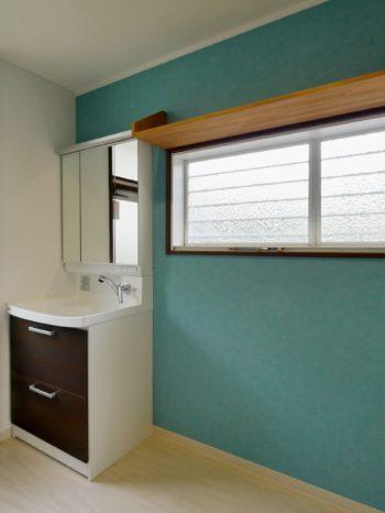長岡京市の中古住宅丸ごとリフォーム。ブルーの壁に白いクロスの洗面室兼ランドリー室です。新しい洗面台は、クリナップのファンシオ。ボールの周囲が高いので、洗濯物の予洗いや洗顔時の水はね、水垂れを抑えます。
