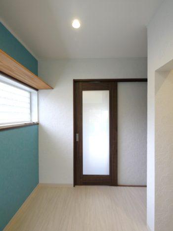 長岡京市の中古住宅丸ごとリフォーム。ブルーの壁に白いクロス、焦げ茶色の真ん中にガラスがはまった引き戸があります。洗面室兼洗濯室です。引き戸を開けるとキッチンです。