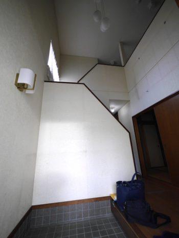 長岡京市の中古住宅丸ごとリフォーム。リフォーム前の玄関です。吹き抜けで天井が高いです。白いクロスの壁には、物がかけられていたであろうシミがあります。