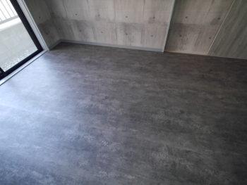 向日市の中古住宅リノベーション。1階の和室を洋室にリフォームしました。ご主人のトレーニングルームとして使われる為、お店などでも使われる業務用の強いシートを床に貼りました。床下も補強してあります。コンクリートの打ちっぱなしの床に、黒い石の床のように見えますがどちらもクロスとシートです。