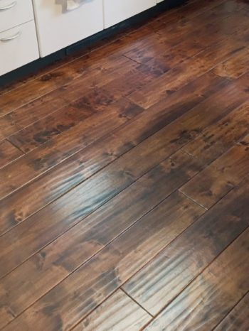 向日市の中古住宅リノベーション。リフォーム前のキッチンの床。リビングの床もこのフローリングです。わざとムラがあるような、光沢のある焦げ茶色の床材です。