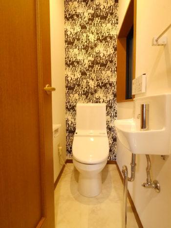 向日市の中古住宅リノベーション。リフォーム後の2階のトイレです。ドアを開けた正面、便器の後ろ側の壁だけを柄クロスに。白と黒のアルファベットが書かれていてトイレの良いアクセントになりました。