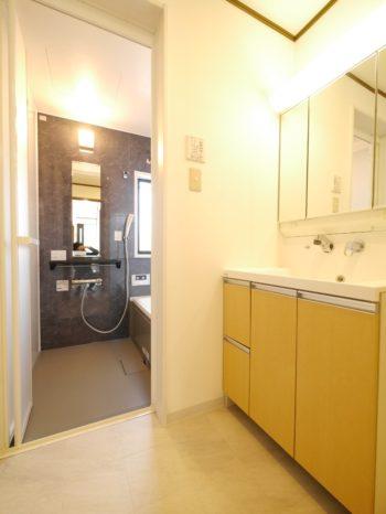 向日市の中古住宅リノベーション。リフォーム後のお風呂場前の洗面室。元々あった洗面台はLIXILピアラ。2人並んで使える90cm幅。ハイバッグガードで水はねも気にならず掃除もしやすい優れものです。三面鏡の裏が収納になっていてたくさん収納出来ます。この洗面化粧台は元々あったもの。