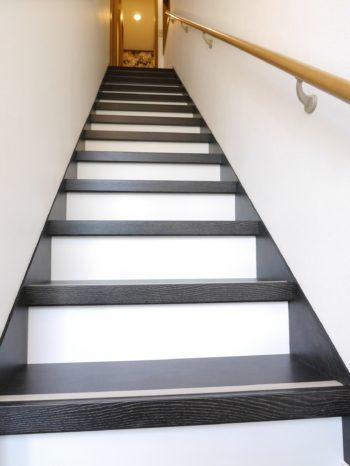 向日市の中古住宅リノベーション。リフォーム後の階段です。踏み面は黒っぽい木目調、前から正面から見える蹴込み板は壁と同じ白のクロスで、モノトーの階段になりました。