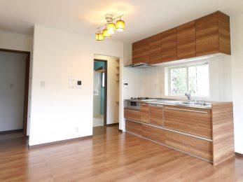 長岡京市の中古住宅丸ごとリフォーム。リフォーム後のキッチン。キッチンの左奥に洗濯室と、1階の洗面スペースがある。